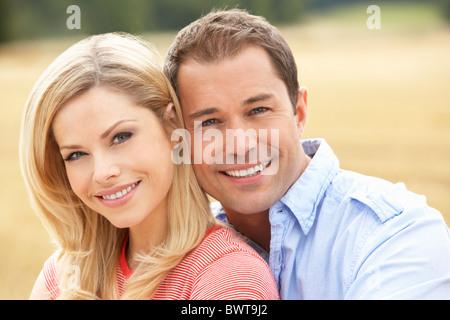 Paar sitzt auf Strohballen In abgeernteten Feld - Stockfoto