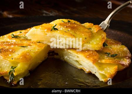 Kartoffel Galettes oder Anna garniert mit frischer Thymian, Salz und Pfeffer würzen und auf einem rustikalen Teller - Stockfoto
