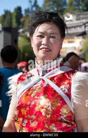 Naxi Frau trägt eine bunteste Kostüm, Lijiang, Provinz Yunnan, China - Stockfoto