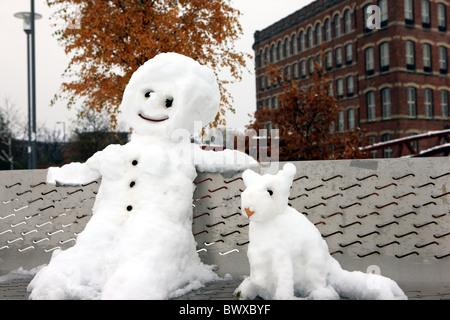 Schneemann und Hund sitzt auf einer Parkbank - Stockfoto