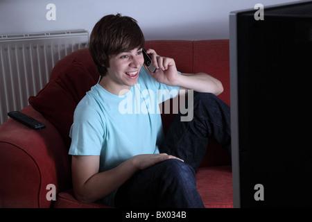 Junger Mann hält eine Telefon Lächeln auf den Lippen und vor dem Fernseher