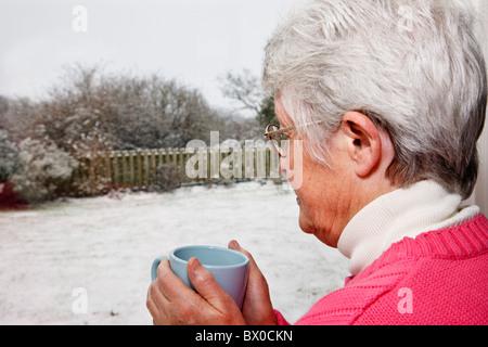 Ältere ältere Frau OAP Dame alleine mit einem heißen Getränk und mit Blick durch ein Fenster Schnee im Garten. Großbritannien - Stockfoto