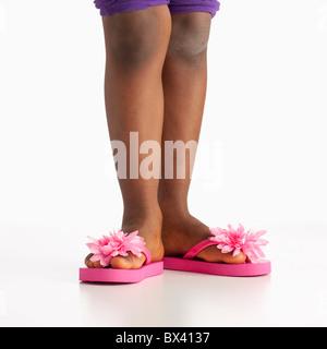 Eine Mädchen trägt Flip Flops mit rosa Blüten - Stockfoto