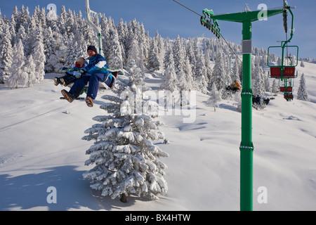 Ein Vater und sein Sohn fahren eine Sessellift zusammen in Velika Planina, Slowenien. - Stockfoto