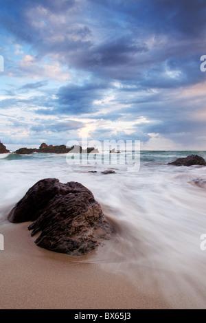 Wellen-Rennen rund um lone rock Freathy Strand Whitsand Bay Cornwall UK Europe - Stockfoto
