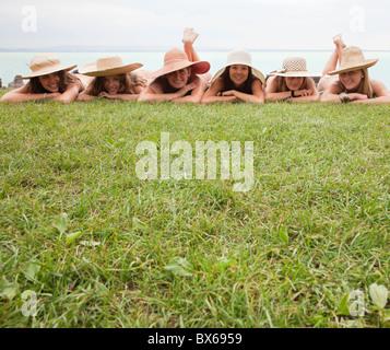 Frauen in Strohhüte liegen auf Rasen - Stockfoto