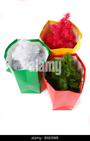Bunte Geschenke-Beutel, gefüllt mit einem kleinen, künstlichen Weihnachtsbaum. - Stockfoto