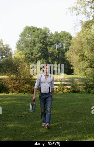 Junger Mann mit Gießkanne - Stockfoto