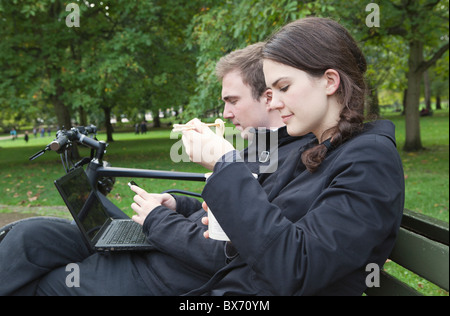 Frau essen Nudeln auf Parkbank - Stockfoto