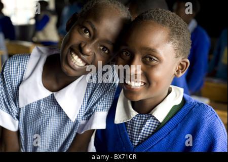 Schulmädchen, zwei Freunde in Schuluniform und lächelnd, Karunga Primary School, Rift Valley in Kenia, Ost-Afrika, - Stockfoto