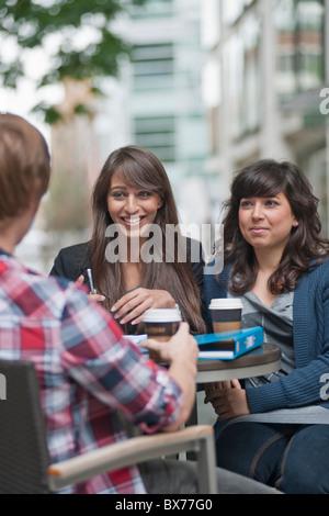 3 Freunde am Café-Tisch sitzen - Stockfoto