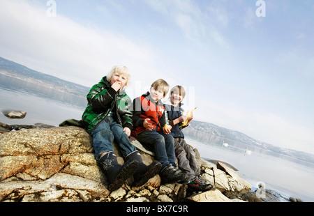 3 jungen Essen Obst am See - Stockfoto