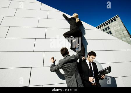 2 Männer helfen Frau über Mauer - Stockfoto