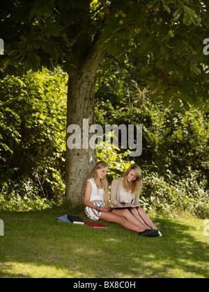 Zwei Mädchen, die unter einem Baum zu arbeiten - Stockfoto