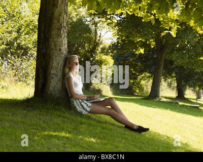 Mädchen entspannt unter einem Baum - Stockfoto