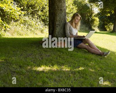 Mädchen auf einem Computer unter einem Baum - Stockfoto