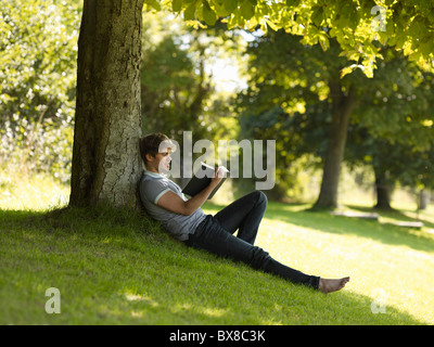 Junge liest unter einem Baum - Stockfoto