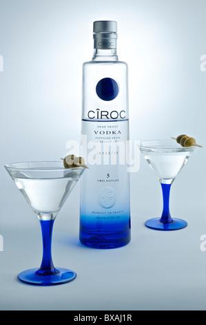 Eine Flasche CIROC Vodka auf weißem Hintergrund mit garniert passenden Cocktailgläser im Vordergrund. - Stockfoto