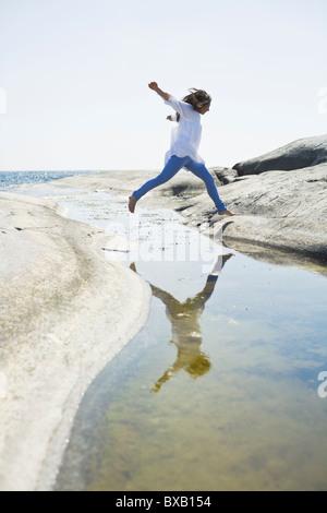 Frau Sprung über Wasser auf Felsen - Stockfoto