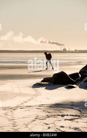 Silhouette des Mannes Schlittschuhlaufen auf dem zugefrorenen See, Fabrik im Hintergrund - Stockfoto