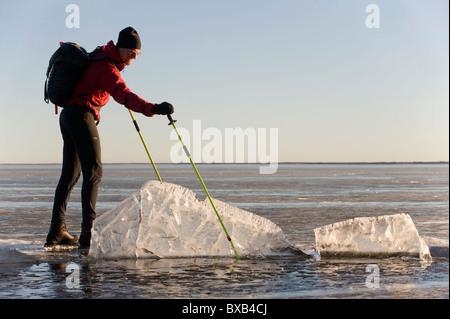 Mann, Schlittschuhlaufen auf dem zugefrorenen See und Blick auf Eisscholle - Stockfoto