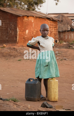 Ein junges Mädchen in ein zerrissenes Kleid steht mit Kanistern in Igamba Dorf, Iganga Bezirk, östlichen Uganda, - Stockfoto