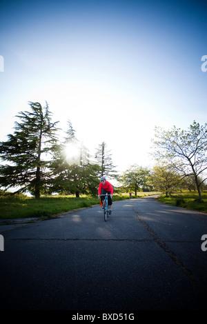 Eine junge Frau Fahrradtouren rund um einen Park bei Sonnenuntergang. - Stockfoto