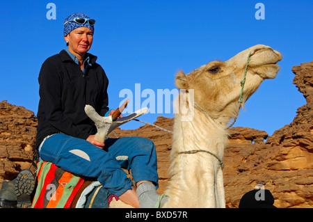 Weibliche Touristen reiten ein Mehari Dromedar in eine skeptische Stimmung bei einem Ausflug in die Acacous Berge, - Stockfoto