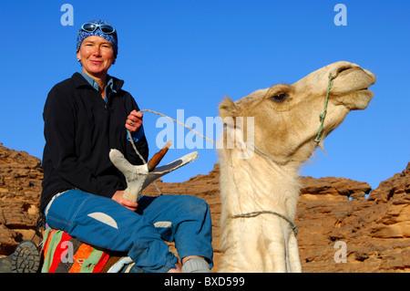 Weibliche Touristen reiten mit stolz auf ein Mehari Dromedar bei einem Ausflug in die Acacous Berge, Wüste Sahara, - Stockfoto