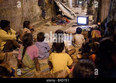 Eine Gruppe obdachloser Menschen Fernsehen in der Nacht auf einem Bürgersteig in Kolkata, Indien. - Stockfoto