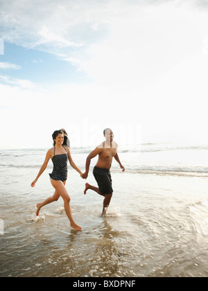 Paar Hand in Hand und laufen am Strand - Stockfoto