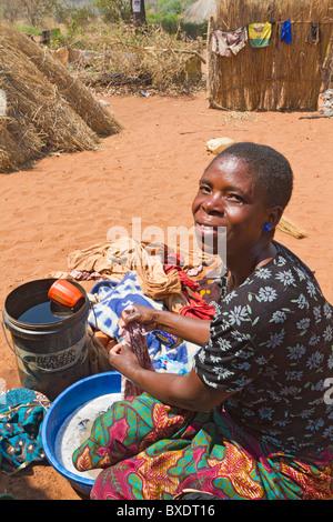 Frau wäscht Familie Kleidung in einer Pfanne in ihrem Dorf Simoonga in der Nähe von Livingston, Sambia, Afrika. - Stockfoto