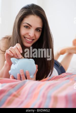 Frau ins Sparschwein Münzen - Stockfoto