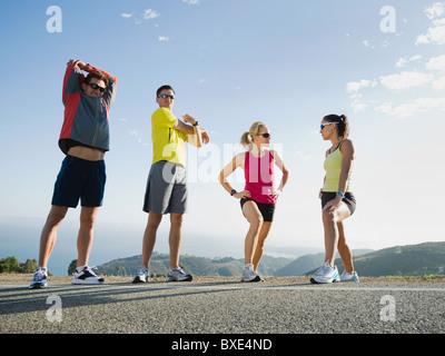 Läufer, die am Straßenrand dehnen - Stockfoto