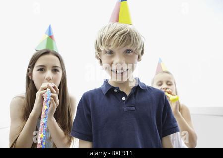 Drei Kinder tragen Partyhüte - Stockfoto