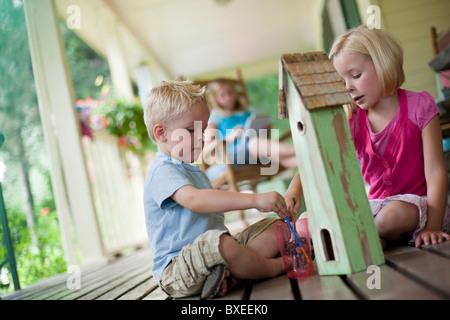 Bruder und Schwester Malerei Vogelhaus zusammen - Stockfoto