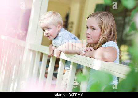 Bruder und Schwester blickte über Veranda Geländer - Stockfoto
