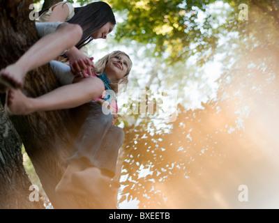 Zwei Mädchen sitzen auf einem Baum - Stockfoto
