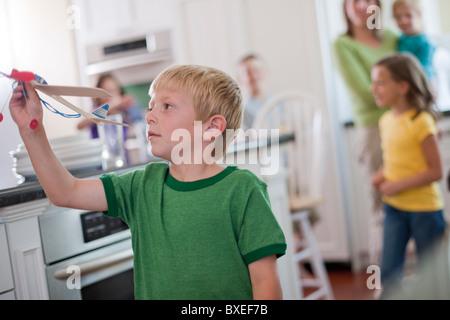 Kleiner Junge spielt mit Spielzeugflugzeug in Küche - Stockfoto