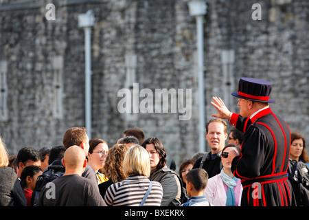 Beefeater mit einer Reisegruppe im Tower of London, UK - Stockfoto