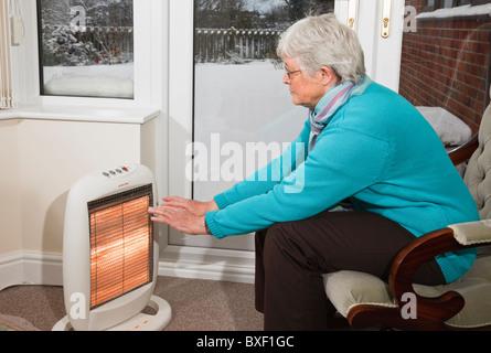 Eine ältere Frau Rentner OAP versuchen, warmen wärmenden Händen drinnen saß vor einer Halogen elektrische Feuer - Stockfoto