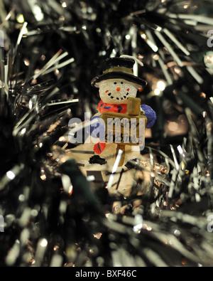 Schneemann Kerze saßen in Lametta und Baum leuchtet - Stockfoto