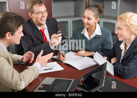 Porträt von vier erfolgreiche Menschen rund um den Tisch versammelt und diskutieren eine neue Geschäftsstrategie - Stockfoto