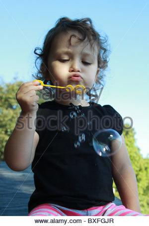 Ein drei Jahre altes Mädchen bläst Seifenblasen mit einer Blase Wand. - Stockfoto