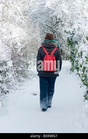 Frau zu Fuß entlang einer Schnee bedeckten Strecke in Redditch, Worcestershire. - Stockfoto