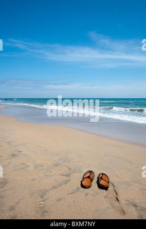 Paar Hausschuhe an einem einsamen Strand von Nilaveli, Trincomalee, Sri Lanka Ostküste. - Stockfoto