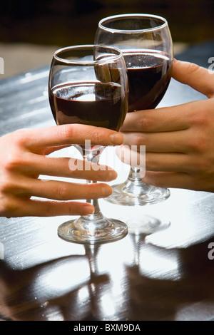 Symbolisches Bild der Gläser Rotwein in Menschenhand - Stockfoto