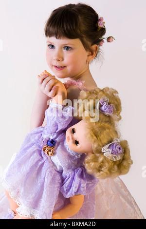 Isoliert auf weiße süße Brünette Mädchen im rosa Kleid hält ihre Puppe - Stockfoto