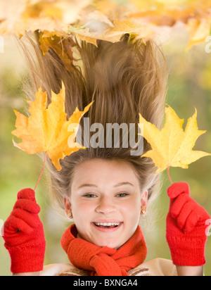 Porträt des Lachens jungen Mädchens hält zwei Ahornblätter - Stockfoto