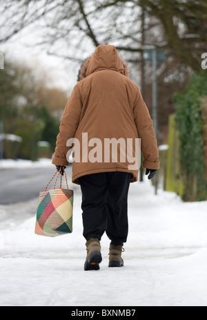 England West Sussex Chichester mittlere gealterte Frau in warme Kleidung Shopping Tragetasche und Wandern auf vereisten - Stockfoto